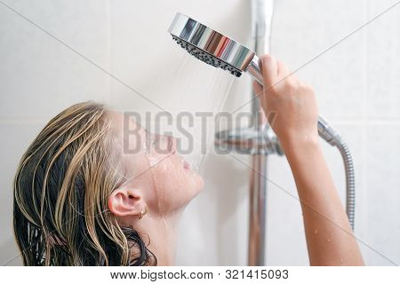 Relaxing Woman In Bathroom Holds The Shower In Hands With Stream Of Water. Portrait Of A Young Woman