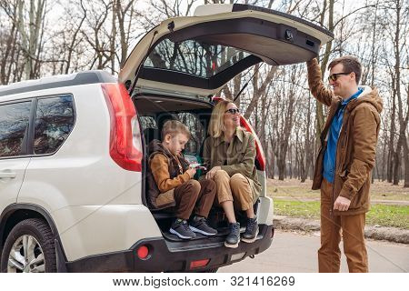 Young Family Packing For Car Travel. Putting Bags Into Trunk. Road Trip