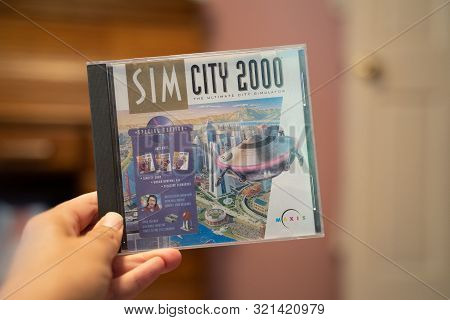 Scandia, Mn - September 10, 2019: Hand Holds Up A Sim City 2000 Cd-rom Game, Published By Maxis, Fro