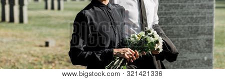 Panoramic Shot Of Senior Man Near Woman With Flowers On Funeral