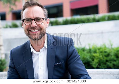 Portrait Of Smiling Mature Businessman Sitting At Outside Office Building