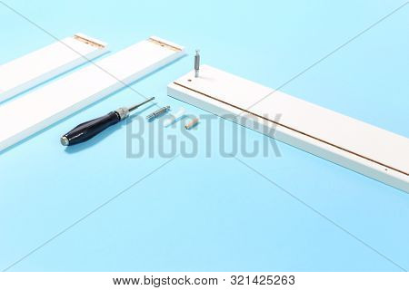 Tools For Assembly Of Flat Packed Furniture On Blue Background. White Diy Funiture Parts With A Scre