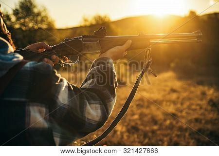 Hunter With Shotgun Gun On Hunt. Illegal Hunting Poacher In The Forest. American Hunting Rifles. Hun