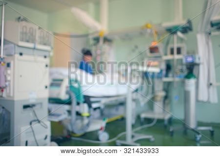 Critically Ill Patient Surrounded By Medical Technologies In The Icu. Female Doctor Stands By Patien