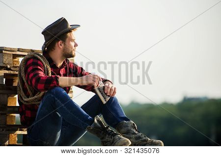 Evening Time. Farmer Drink Alcohol Enjoy View From His Farm. Watching Sunset. Farmer Cowboy Handsome