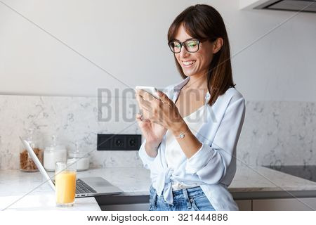 Image of a young beautiful cheerful happy business woman indoors at home at the kitchen using laptop computer using mobile phone.