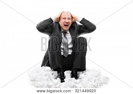 Business problems and failure at work concept - loud shouting or screaming tired stressed businessman hands covering ears for silence sitting floor on crumpled torn paper document heap white isolated