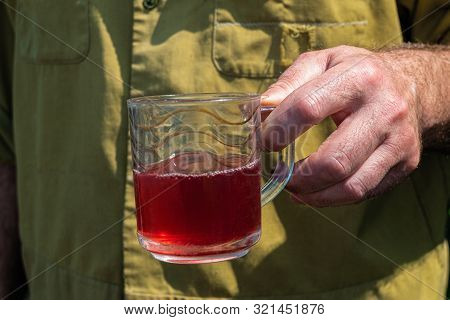 Simple Working Agrarian Man With A Glass Mug Of Compote In His Hand