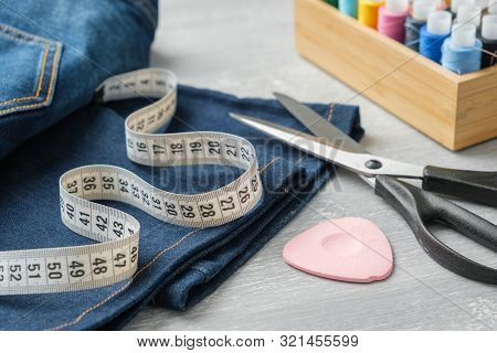 Shortening Jeans With Scissors, Measuring Tape And Chalk. Jeans Cutting Or Repair.