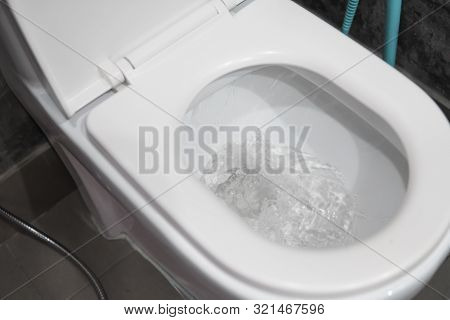 Water Flushing In Toilet Bowl. White Hanging Toilet Seat On White Toilet In The Home Bathroom With G