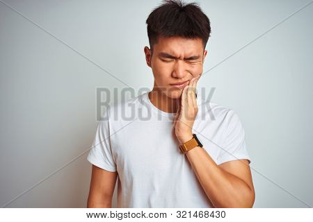 Young asian chinese man wearing t-shirt standing over isolated white background touching mouth with hand with painful expression because of toothache or dental illness on teeth. Dentist concept.