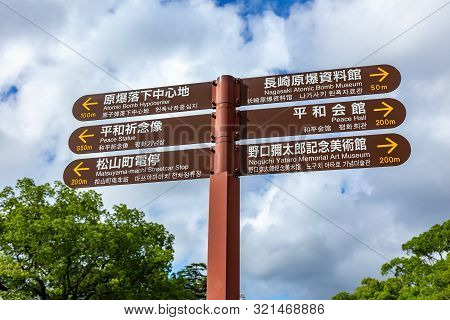 Nagasaki, Japan - 11 July 2019 - Walkway Direction Sign Stands Against Cloudy Blue Sky At Nagasaki A