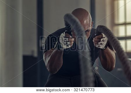 Strong athlete doing exercises with rope at fit gym. Bald african man working out with ropes at  fit gym. Fitness strong man pulling rope at fitness center.