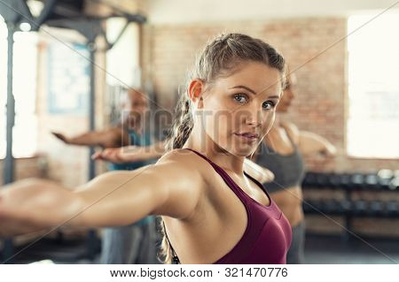 Closeup face of determined woman doing aerobic exercises at gym standing with arms outstretched. Determined young woman in sportswear stretching arms in gym. Beautiful girl in yoga pose with class.