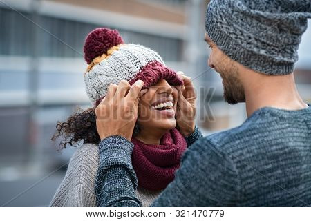 Loving multiethnic couple having fun outdoor in winter. Young man covering eyes his girl with woolen cap. Cheerful guy and smiling african woman playing in winter outdoor.