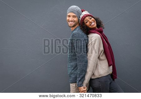 Young multiethnic couple holding hands while standing and leaning on each other back. Happy man and black woman standing back to back and smiling against grey wall with copy space.