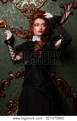 Historical reconstruction of the Victorian era. Portrait of an elegant woman in vintage  dress and hairdo. Baroque era.