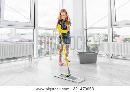 Diligent little girl mopping light floor