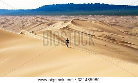 Men Walking In The Mongolian Desert Sand Dunes. Young Men Walking Golden Sand On A Bright Summer Day