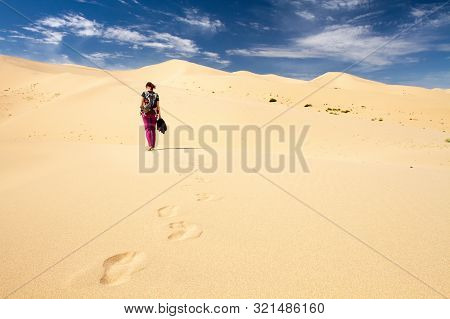 Woman Walking In The Mongolian Desert Sand Dunes. Young Woman Walking Golden Sand On A Bright Summer