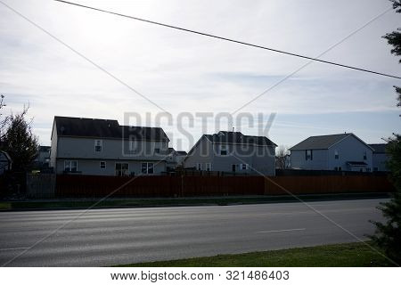 Two Story Single Family Tract Homes, Behind Wooden Stockade Fences, In Joliet, Illinois, During Dece