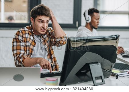 Selective Focus Of Discouraged Programmer Holding Hand On Head While Looking At Monitor Near African