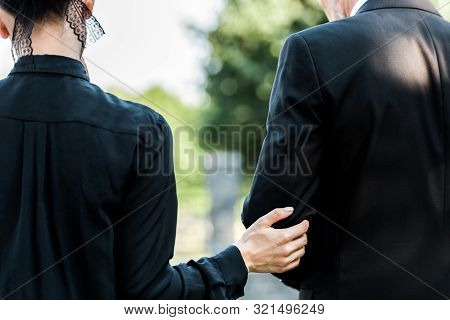 Cropped View Of Woman Touching Elderly Man On Funeral