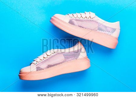 Sneakers Isolated On Blue Background, Fashion. Sport Shoes. Pair Of Pink Sport Shoes On Blue Backgro