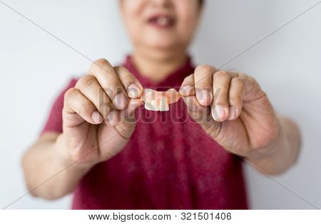 Senior Asian Woman Is Holding Dentures In Hands,dental Prosthesis,false Teeth,close Up