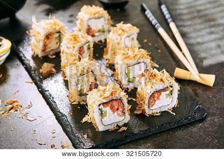 Macro shot of uramaki sushi rolls with cream cheese, salmon, tuna shavings or dried bonito, cucumber, nori. Taking portion of fresh katsuobushi roll in Japanese restaurant closeup