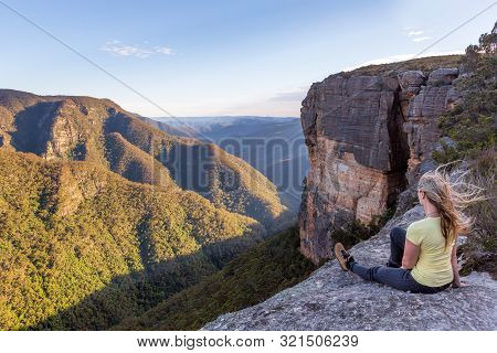 A Female Takes In Magnificent Views From The Cliff Top  Of The Mountainous Landscape, With Morning R