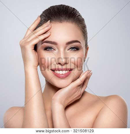 Beauty face of the young beautiful smiling woman  with a fresh healthy skin. Closeup portrait of an attractive caucasian female. Skin care concept. Woman with a smokey eye makeup. Beauty treatment.
