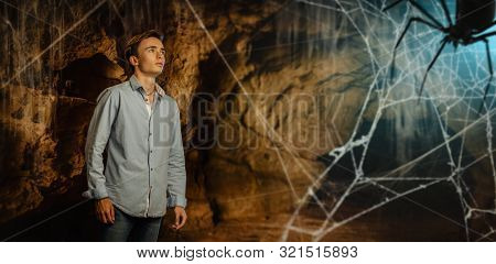 A full length portrait of a young goodlooking guy in the cave with the spider. Men casual fashion, Jedi.