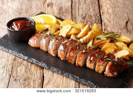 Traditional Baked Pork Tenderloin With Potato Wedges Close-up On A Slate Board. Horizontal