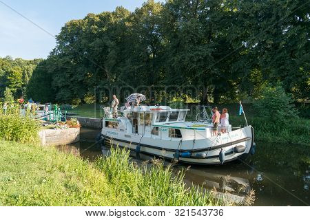 Houseboats With Tourists Pass Through River Locks On The River Oust Near Josselin In Brittany