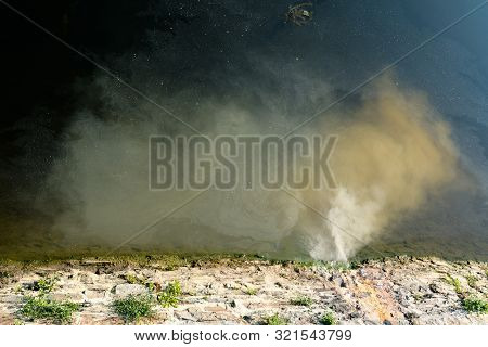 Detail View Of Sewage And Dirty Water Spilling Into A Clean River