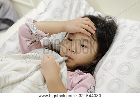 Asian Child Girl Is Sick And Has A Thermometer In Her Mouth While Lying On The Bed.  Sick Child With