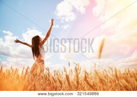 Happy woman enjoying the life in the sunny field. Nature beauty, blue sky,white clouds and field with golden wheat. Outdoor lifestyle. Freedom concept. Woman jump in summer field