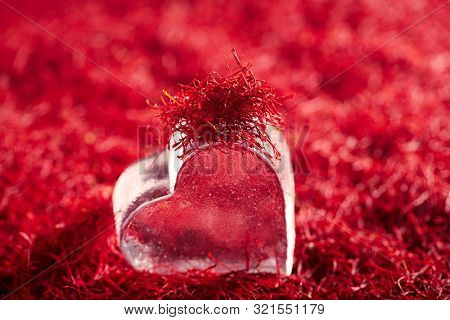 saffron threads background with glass heart, truly color, huge amount of spice , soft focus
