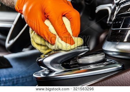 A man cleaning car interior panels and dashboard with yellow microfiber cloth. Car detailing or valeting concept. Selective focus. Car detailing. Cleaning with sponge. Worker cleaning. Car wash concept solution to clean poster