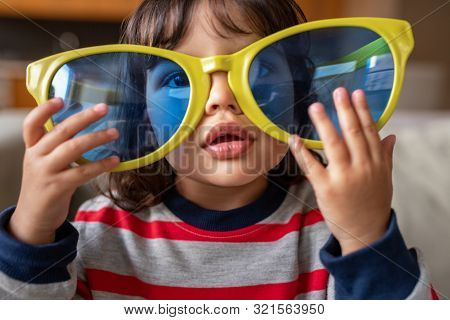 Adorable Little Girl Playing With Oversized Novelty Sunglasses At Home