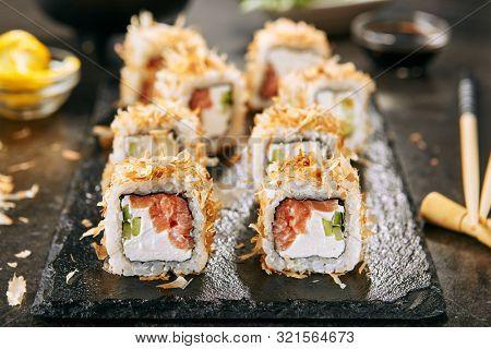 Macro shot of uramaki sushi rolls with cream cheese, salmon, tuna shavings or dried bonito, cucumber, nori. Taking portion of fresh katsuobushi roll in Japanese restaurant closeup poster