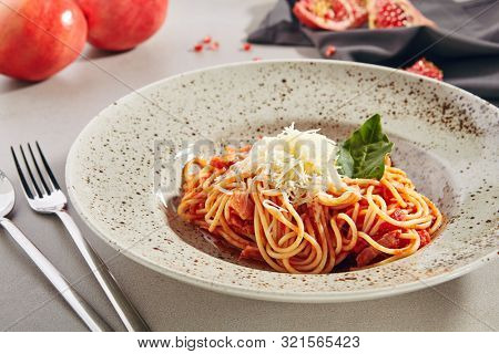 Classical Italian spaghetti with Amatriciana sauce, grated cheese and greens close up. Traditional homemade pasta with salsa alla matriciana based on guanciale, pecorino cheese, tomato, and onion