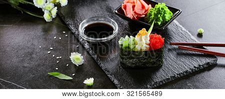 Delicious gunkan with cucumber and masago caviar. Japanese cuisine restaurant menu item. Traditional eastern dish, national cooking. Tasty sushi, oriental food on wooden platter closeup