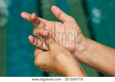 Trigger Finger, Senior Woman's Left Hand Massaging Her Ring Finger, Suffering From Pain, Close Up An