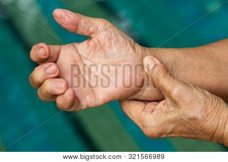 Trigger Finger, Senior Woman's Left Hand Massaging Her Right Hand Suffering From Pain, Close Up And