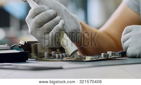 Repairman Putting Thermal Paste On Processor Of Graphics Chipset At Workshop.