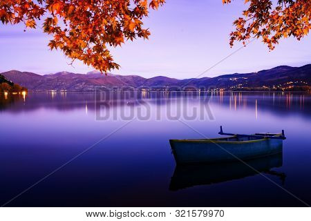 Evening Autumn Mood With A Blue Tint On The Lake With A Boat. Kastoria, Greece.