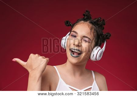 Image of happy punk girl with bizarre hairstyle pointing finger at copyspace while listening to music with headphones isolated over red background poster