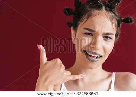 Image of joyful punk girl with bizarre hairstyle and makeup smiling at camera while gesturing shaka or hang loose sign isolated over red background poster